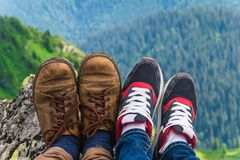 Landscape, travel, tourism. A pair of feet in the shoes against the background of the mountains. Horizontal frame Stock Photography