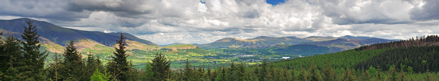 Landscape panorama. Sweeping panorama with dramatic sky,sunlit valley,mountains and a pine foreground. The town of Keswick can be seen in the sunlit valley Stock Images
