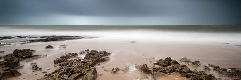 Landscape panorama long exposure image of rocks and sandy beach Royalty Free Stock Photos
