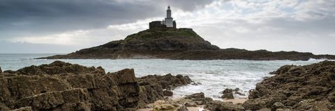 Landscape panorama of Mumbles lighthouse in Wales with sunbeams Stock Photography