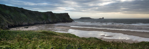 Landscape panorama Rhosilli Bay beach at sunset with moody sky Royalty Free Stock Images