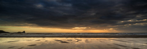 Landscape panorama Rhosilli Bay beach at sunset with moody sky Stock Photography