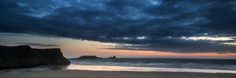 Landscape panorama Rhosilli Bay beach at sunset with moody sky. Landscape panorama Rhosilli Bay beach at sunset with dramatic sky Royalty Free Stock Image