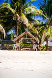 Landscape of paradise tropical island with palms, cottages and white sand beach Stock Image