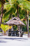 Landscape of paradise tropical island with palms, cottages and white sand beach Royalty Free Stock Photography