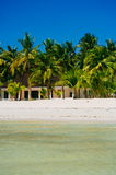 Landscape of paradise tropical island with palms, cottages and white sand beach Royalty Free Stock Images