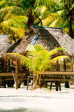 Landscape of paradise tropical island with palms, cottages and white sand beach Stock Photos