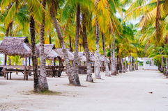 Landscape of paradise tropical island with palms cottages and white sand beach Stock Photos