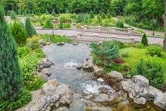 Landscape Park.Waterfall, bridge.  Beautiful ornamental plants and trees. Stock Photo