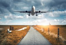 Landscape with passenger airplane is flying over the asphalt roa royalty free stock photography
