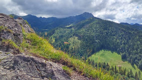 Landscape with a pasture below and a mountain range under the clouds, a sunny summer day. View from Nosal Mountain, Tatry, Poland. A mountain landscape with a royalty free stock photography