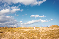 Landscape with people. Three people standing in a field on the rocks with arms raised Royalty Free Stock Images