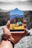 Landscape on a phone screen. Colorful landscape with alpine mountain valley and wooden house on a screen of smartphone against monochrome background. Travel and Royalty Free Stock Images