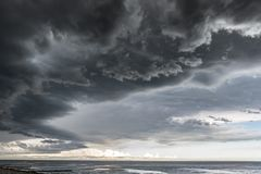 Approaching storm cloud with rain over the sea. Landscape photo of a beach and dramatic thunderstorm clouds over the sea or the ocean Royalty Free Stock Photography