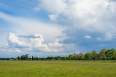 Landscape photo of a green field with cloudy sky stock images