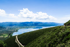 Landscape Photo of Green Mountain in Front of Body of Water Under Blue and White Cloudy Sky Royalty Free Stock Images