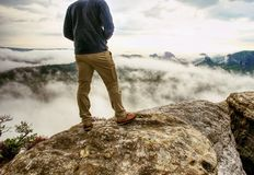 Landscape photograper with camera ready in hand. Man climbed up. On exposed rock for fall photos with his digital camera. Cliff above misty autumn landscape royalty free stock images