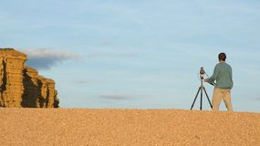 Landscape photographer. A landscape photographer lining up a late evening shot of coastal cliffs Royalty Free Stock Images