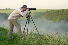 Landscape photographer. Landscape photography at sunrise taking pictures on a slr Stock Photography