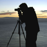 Landscape Photographer. Silhouette of photographer with tripod Stock Photography