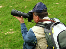 Landscape photographer. Photographer taking pictures on green grass. Location: Eastern Europe Royalty Free Stock Images