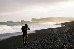 Landscape photographer in Iceland. Ic photo tour photographs the ocean. View of Cape Dyrholaey from Reynisfjara Beach, Iceland stock image