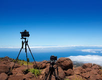 Landscape photographer tripods and camera. S over high mountain over clouds Royalty Free Stock Photos