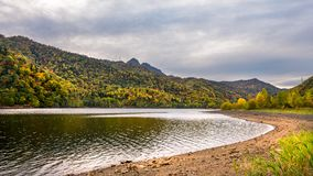 A lake with autumn five color tree hill in the Afternoon. Landscape photography of autumn trees hill with a lake in the afternoon cloudy sky Stock Image