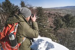 Landscape photography: a man hiker with a backpack shoots a landscape in a winter forest. High in the mountains Royalty Free Stock Image