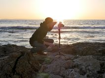 Landscape photography shot with photographer setting up his camera on a beach at sunset. stock photo