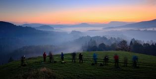 Landscape photography workshop. Photographers on course during mountain sunrise. Hills and villages with foggy morning. Fog in Cze. Ch Republic stock photography