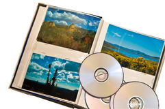 Landscape Photos CD and Album. A group of travel photos on top of a photo album with some CD's.  Concept for backing up your images onto a CD or DVD for safety Stock Photography