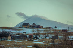 Landscape picturesque view little village at the hills. Landscape picturesque view of a little village with few little wooden houses at the hills with snowy Royalty Free Stock Images