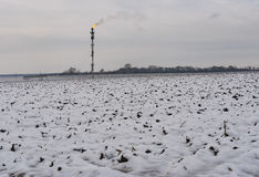 Landscape with pipe of burning oil-well gas on an agricultural field at winter season Stock Photos