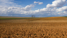 Landscape plows Country Land and Crops. Panoramic landscape with  fallow land recently plowed and cereal crops. A sunny day with cottony clouds Stock Photography