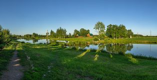 Landscape with a pond at sunset in Central Russia. The landscape at sunset is rich in colors. Illuminated by Golden sunlight, fields, meadows, trees, hills and stock photography