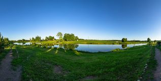 Landscape with a pond at sunset in Central Russia. The landscape at sunset is rich in colors. Illuminated by Golden sunlight, fields, meadows, trees, hills and royalty free stock images