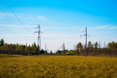 Landscape is with power lines, field, forest and sky with clouds. Landscape is with power lines, field, forest and sky Stock Photo