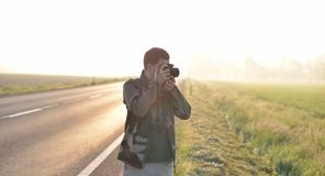 Landscape professional photographer taking a picture near a road. With the sunrise in the background Royalty Free Stock Photo