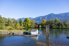 Landscape of quiet backwater with an old pier in the backwaters. Autumn landscape with an old abandoned rotten wooden pier in the bay of the Columbia River with stock photos