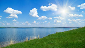 Landscape with quiet water of lake. Summer landscape with quiet water of lake, blue cloudy sky and green grass Royalty Free Stock Photo