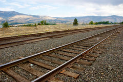Landscape with a railroad track and mountains in the background. Railroad tracks going into the distance with mountains and sky in the background Stock Photo
