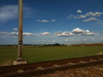 Landscape with railway line, green pastures, blue skies and scattered clouds. Railway line in a landscape against a blue sky with scattered clouds Stock Photo