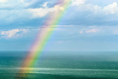 Landscape with a rainbow after the rain. Beautiful landscape with a rainbow after the rain. focus on the waves in front of the frame and rainbow Stock Image