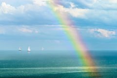 Landscape with a rainbow after the rain and sailboats Royalty Free Stock Images