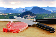 Landscape and raw pork meat and knives on the cutting board in the foreground Stock Photos