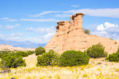 Landscape, red buttes in green landscape under blue sky. Royalty Free Stock Photos