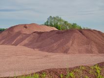 Red Rock Quarry Gravel Pit and Stone Pile. Landscape of red rock quarry gravel pit with piles of crushed stone background stock image