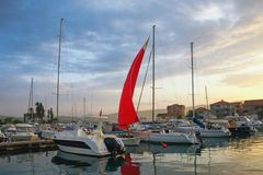Landscape with red sail at sunset. Fishing boats in harbor. Montenegro, Tivat Stock Photos