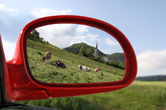 Landscape reflected in the rear view mirror of a r. Sommer Landscape reflected in the rear view mirror of a red car Royalty Free Stock Photography